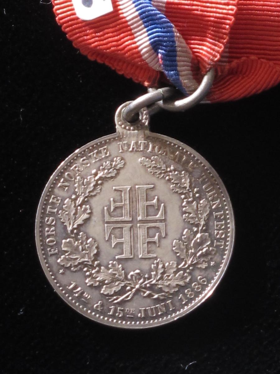 På advers side: en turner og forbundets navn; på revers side:  4F-emblem.