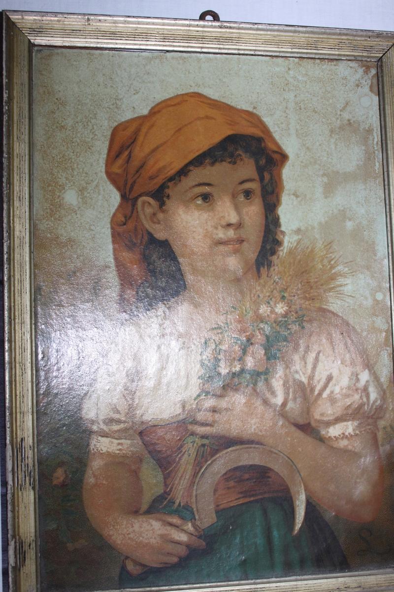 Flicka klädd i vit blus med rött livstycke och blågrön kjol. På huvudet ett rött huckle. I vänster hand håller hon en bukett bestående av blommor och sädesax. I höger hand håller hon en skära.