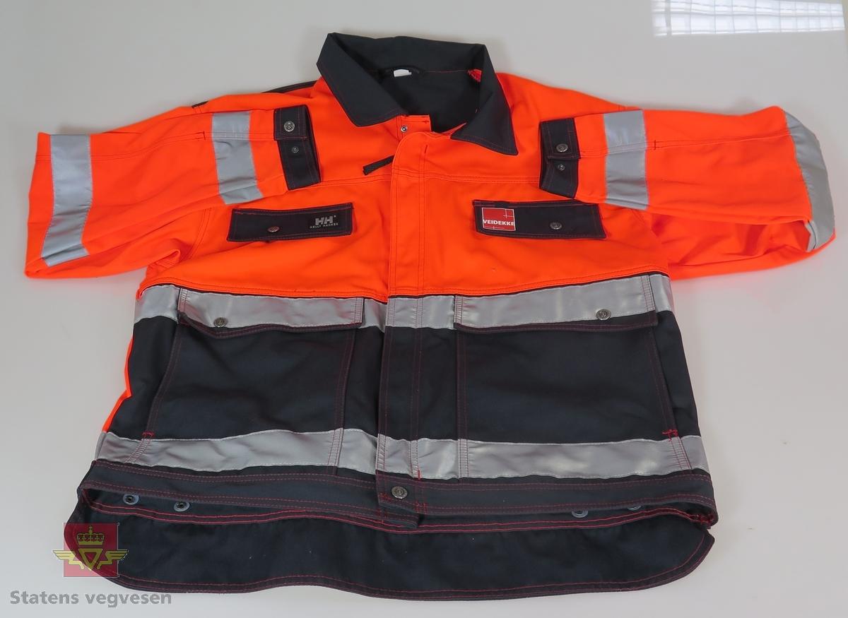 Flerfarget jakke i fluoriserende materiale. Glidelås.  Knepping. Lommer. Veidekke-logo på  venstre brystlomme.