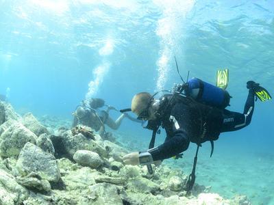Dykker på sjøbunn i klart, lyseblått vann, stener på bunnen.
