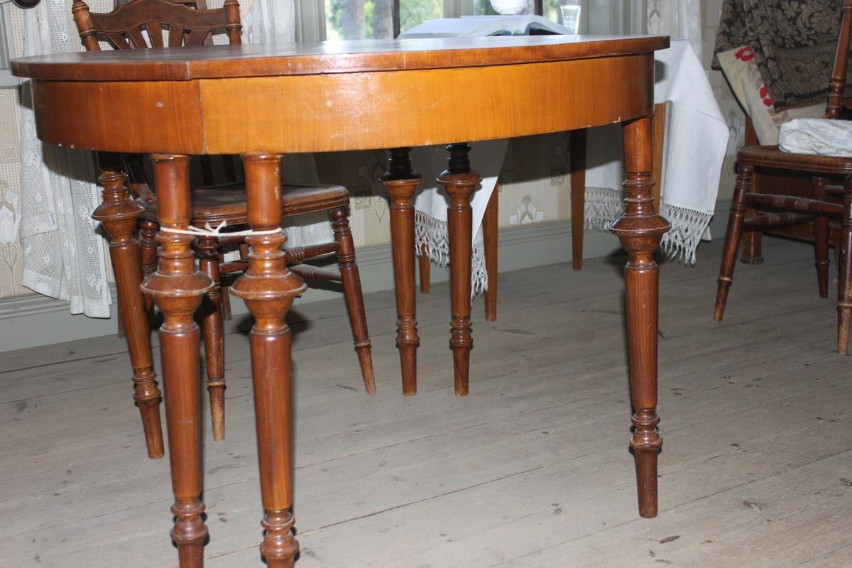 Runt bord som kan delas i två halvmåneformade delar. Bred, slät sarg under skivan. Tre ben till varje, kraftigt profilerade på övre halvan. Tappar i ena skivan med motsvarande hål i andra delen.