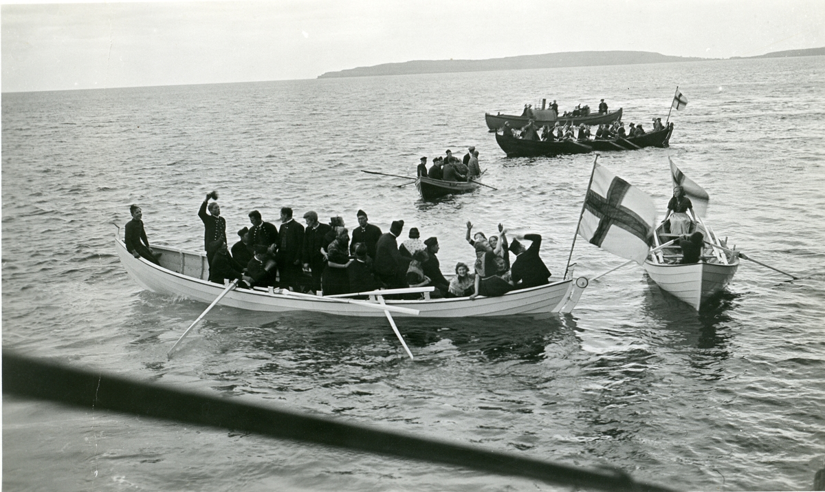 """Færøyene 01.08.1932. Småbåter med mange mennesker hilser DA """"Stavangerfjord""""."""