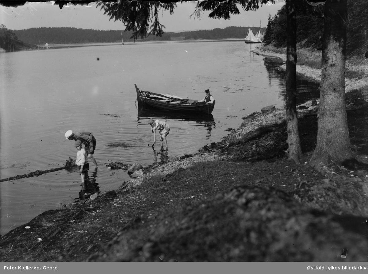 Gjøvik, ukjent sted. Tre gutter leker i strandkanten, ukjent mann i robåt, Seilbåter i bakgrunnen.