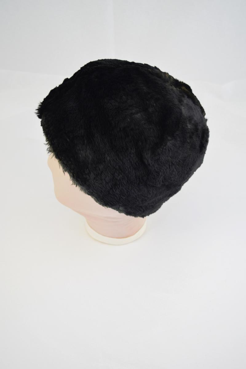 Hatt eller lue av pels. Rund form. Foret med ull dekket av et tynnere stoff. Foret er sydd med sømmer som former en rose eller stjerne på  innsiden av hatten.