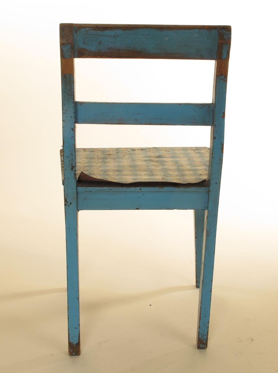 Rette forben, svakt svungne bakben, rett overstykke og horisontalt  ryggbrett. Flatt trapesformet tresete, trukket med blå og hvit rutet, slitt voksduk. Tilstand: løs i limingen, avskrapet og  maling slitt, et lag brunmaling under.