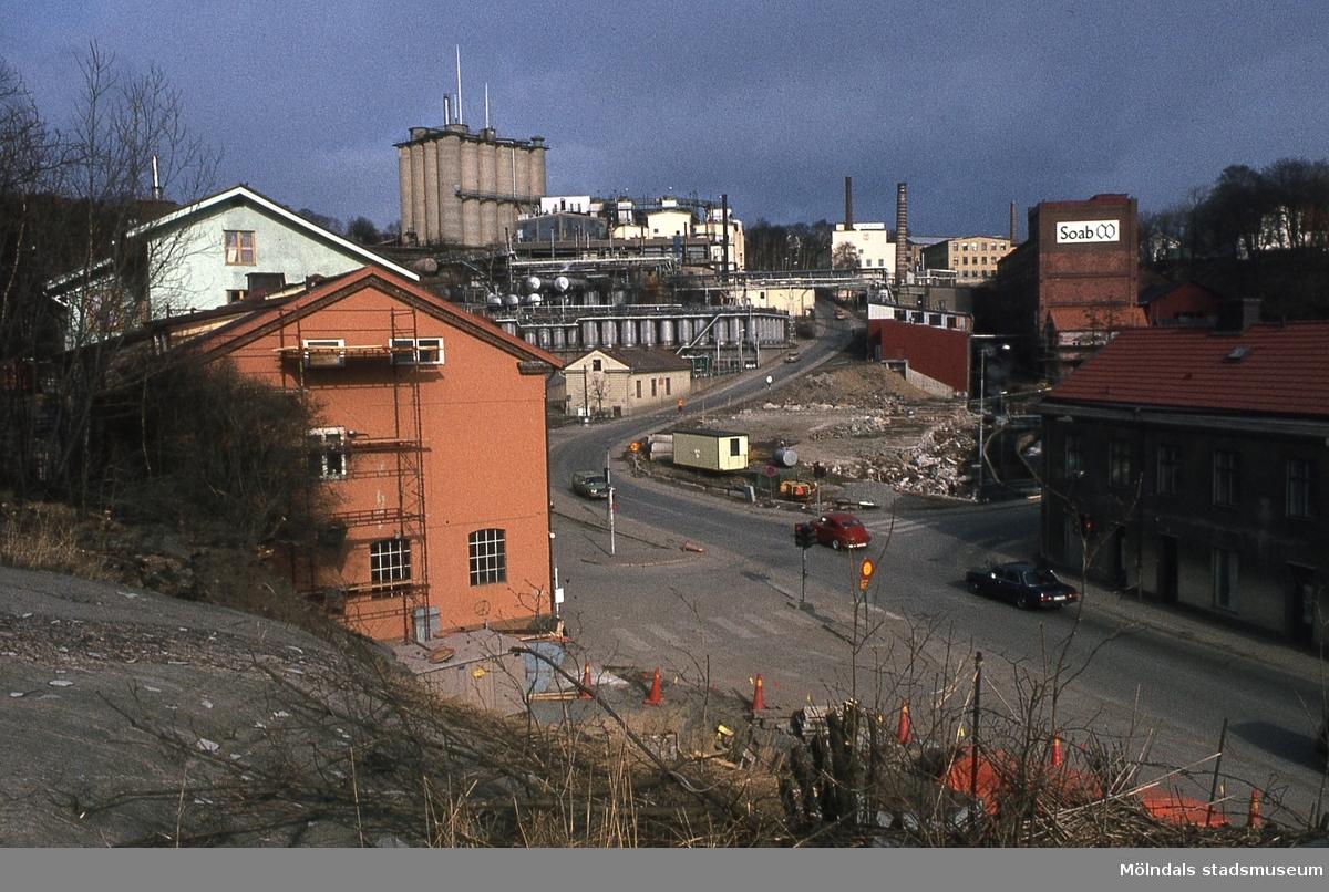 """Bebyggelse vid Kvarnbygatan och Gamla Torget i Mölndal efter rivning av SOAB:s lagerbyggnad, år 1984. Till vänster ses gaveln till huset Kvarnbygatan 41. I mitten industribyggnader tillhörande SOAB samt backen """"Kråkan"""". I bakgrunden till höger ses Stora Götafors och huset närmast till höger är Kvarnbygatan 4 (byggnad 213)."""