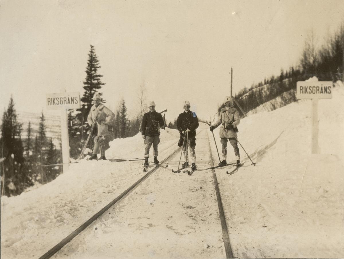 """Landsgränsen mellan Sverige och Norge. Fyra soldater på skidor står på järnvägsrälsen mellan två skyltar med text """"Riksgräns"""". Bakom gruppen syns några träd och berg."""