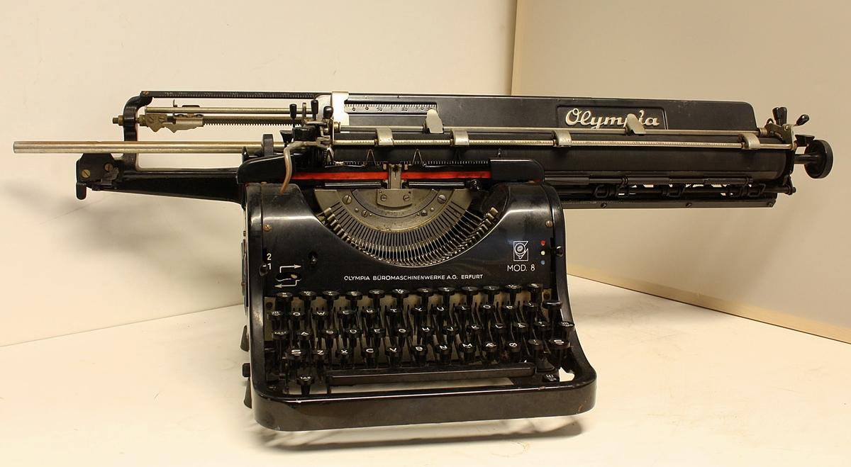 Sort maskin med tastatur foran og veldig lang rull oppe.