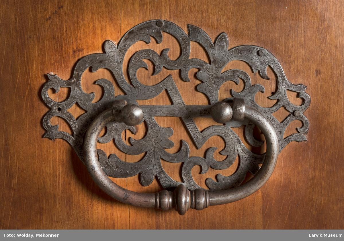 Dragkisten har 4 skuffer med messinghåndtak og beslag på nøkkelhull, gjennombrutt jernbeslag med håndtak på sidene, tunget sarg 4 bukkeben. Nøkkel.