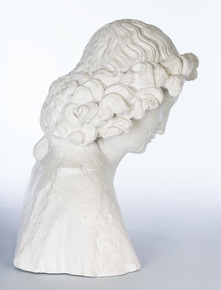Forestiller apostelen Johannes. Gipsavstøpning av original fra Nidarosdomens vestfront. Originalen er fra slutten av 1200-tallet, og viser tydelig påvirkning fra fransk høygotikk. Bysten er avskåret på tvers et stykke nedenfor skuldrene (originalen er i hel figur).