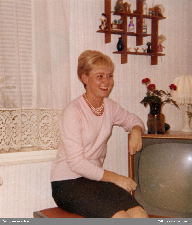 Ninnie Tobiasson sitter på en stol vid en TV. Hon bodde på Krokslättsgatan 3 mellan åren 1962-1966.