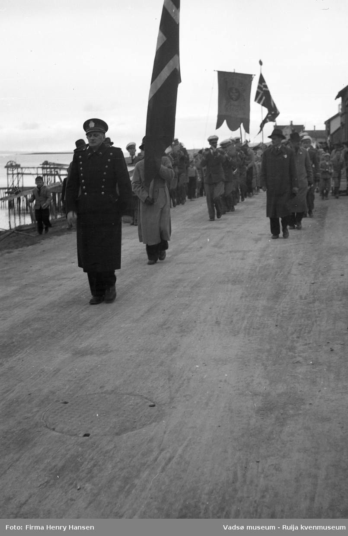 Vadsø 17. mai 1951. Musikkkorps masjerer i Indrebyen, antas å være i Havnegata. Vi ser flagg og fane. Fremst i toget masjerer en politimann som antas å være senere politimester Wickstrøm. Publikum, barn og voksne sees langs 17.maitoget. I venstre billedkant skimter vi sjøen med kaier, hjellbruk og nothjul.