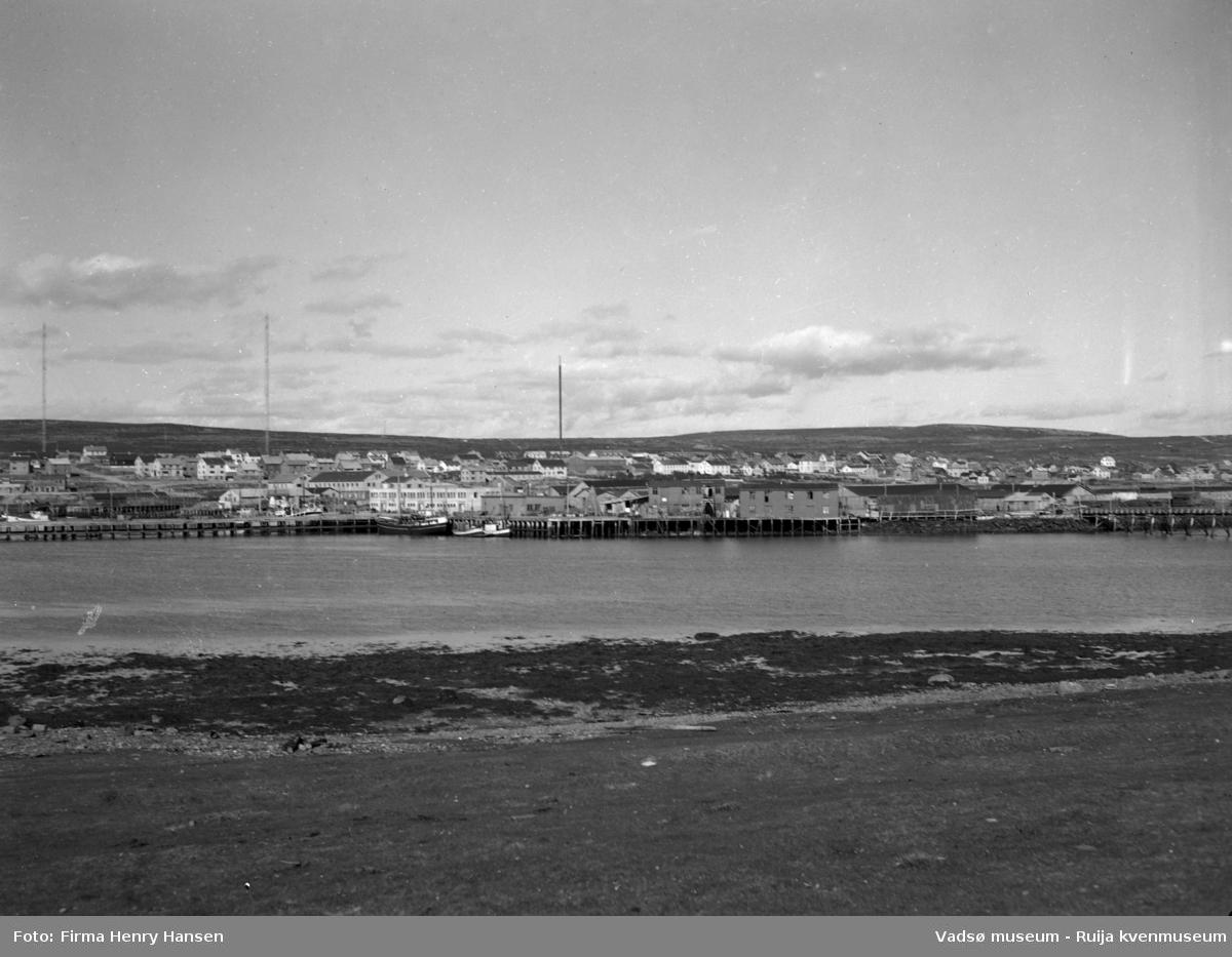 Oversiktbilde Vadsø Sentrum med  deler av Ytrebyen. Bildet er tatt fra Vadsøya mot nordøst. Vi ser havna med piren på dampskipskaia, dampskisekspedisjonen og et fiskebruk midt i bildet. Fiskebåter ligger fortøyd ved kaia. I høyre billedkant ser vi deler av brua over til Vadsøya. Videre ser vi Vadsø sentrum/Midtbyen og deler av Ytrebyen med gjenreisingsbebyggelse. Til venstre i bildet ser vi de to radiomastene. Midt i bildet en ukjent mast.