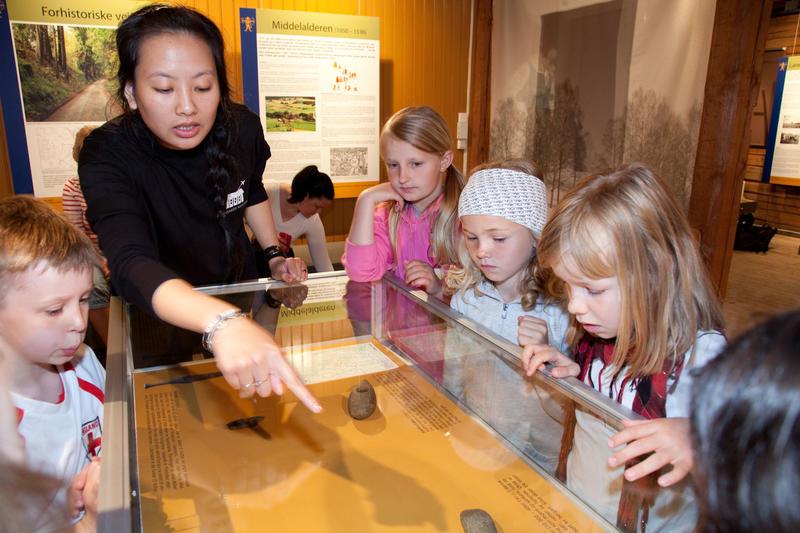 Omviser viser elever fra 3. trinn forhistoriske gjenstander som ligger i et monter.