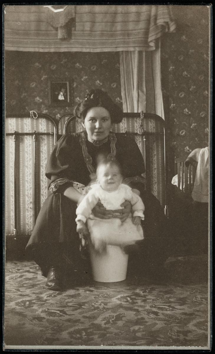 """En kvinna håller i spädbarnspojke som sitter på en hink i ett sovrum. Påskrift på baksida: """"Farmor gratuleras hjärtligt på Sofiadagen 1908 af Stig med mor + far. Kortet taget den 19/4 1908."""""""