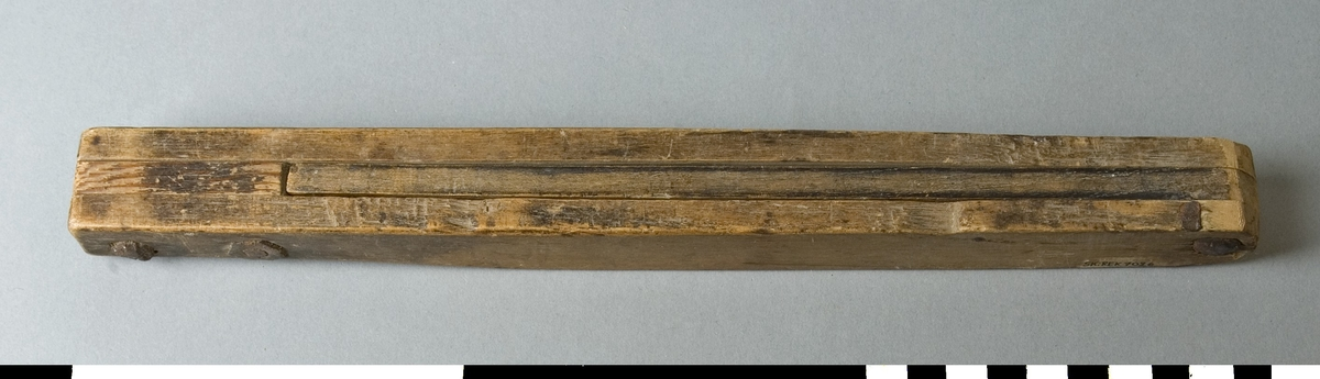 Smygvinkel av trä. Den består av två fasta parallella trästycken som är förbundna med varandra i vardera änden med skruv. Mellan dessa finns en ställbar vinkel som kan ställas i önskad vinkel. Vinkeln är ej låsbar. Skruv och mutter är rostiga.   Funktion: Mätning och markering av vinklar, inställbar