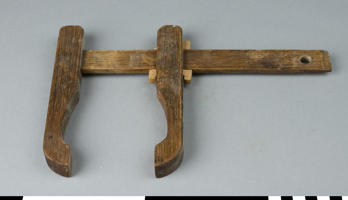 Klämtving av ek. Klämtvingen består av två kloformade trästycken varav det ena är fastlimmat i den övre änden av en linjalliknade skena. Det andra är rörligt och löper genom ett rektangulärt hål längs skenan. I hålet på var sin sida av skenan sitter två kilar med vars hjälp man kan klämma fast de två klorna på de trästycken som skall limmas. På varje klämyta sitter en fyrkantig läderbit fastspikad. I skenans nedre ände finns ett hål för upphängning. Klämtving q är 230 mm lång. 5 st saknar en eller två kilar. Nötta och fläckiga. Kommer troligen från Dahlgrens snickeri i Nacka.  Funktion: Hålla ihop delar som limmas