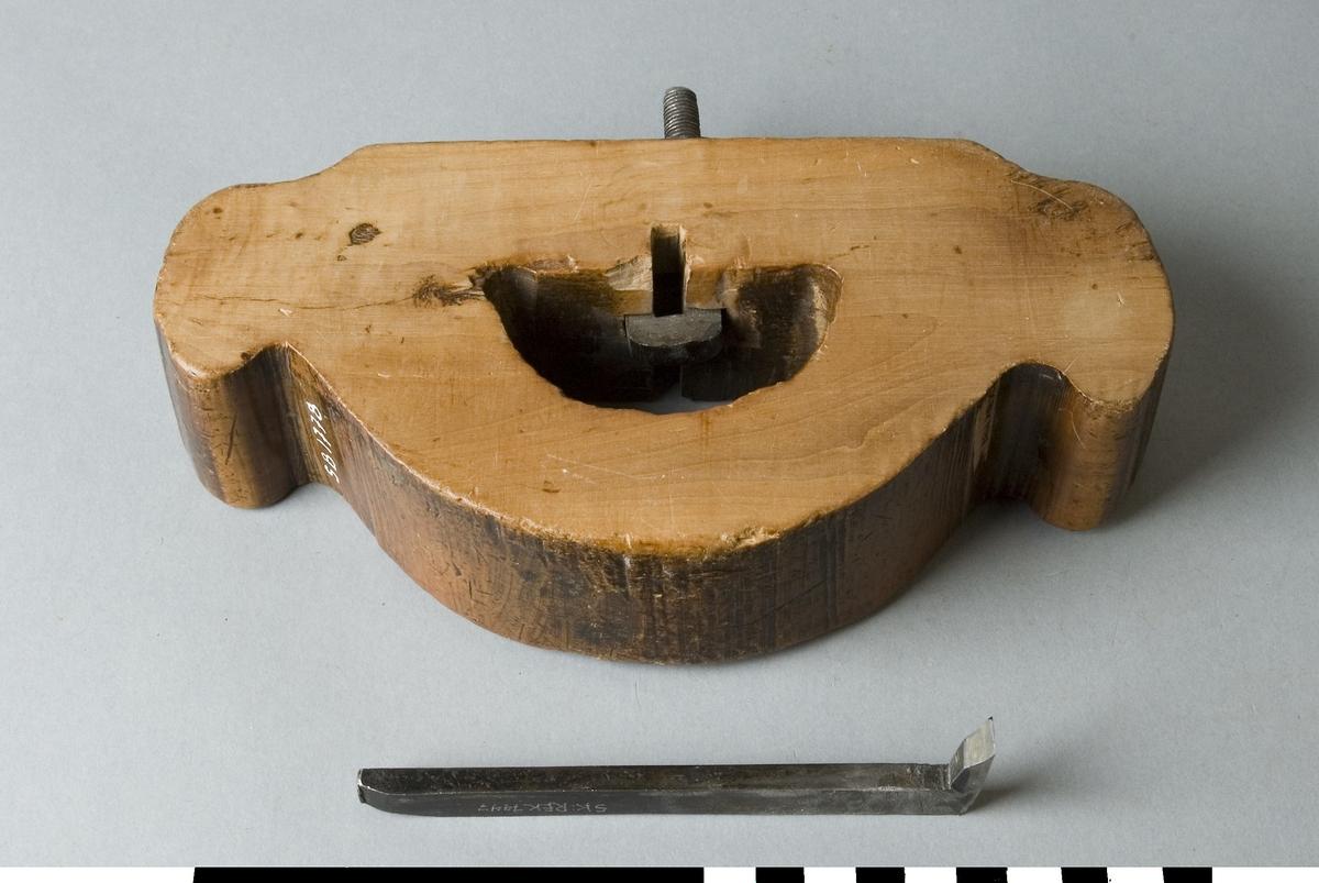 Grundklots av björk. Den är tillverkad i ett stycke och liknar en napoleonhatt med ett bågformat hål genom det som liknar huvudskulten. Från botten till hålet går en skruv som slutar i ett fäste för ett vinkelställt hyveljärn. På skuven sitter en mutter för låsning av järnet. Grundhyveln är avsedd för hyvling  i spår och dylikt tvärs över fibrernas längdriktning.  Funktion: Hyvlar ett spår användbart vid hopfogning av arbetsstycken