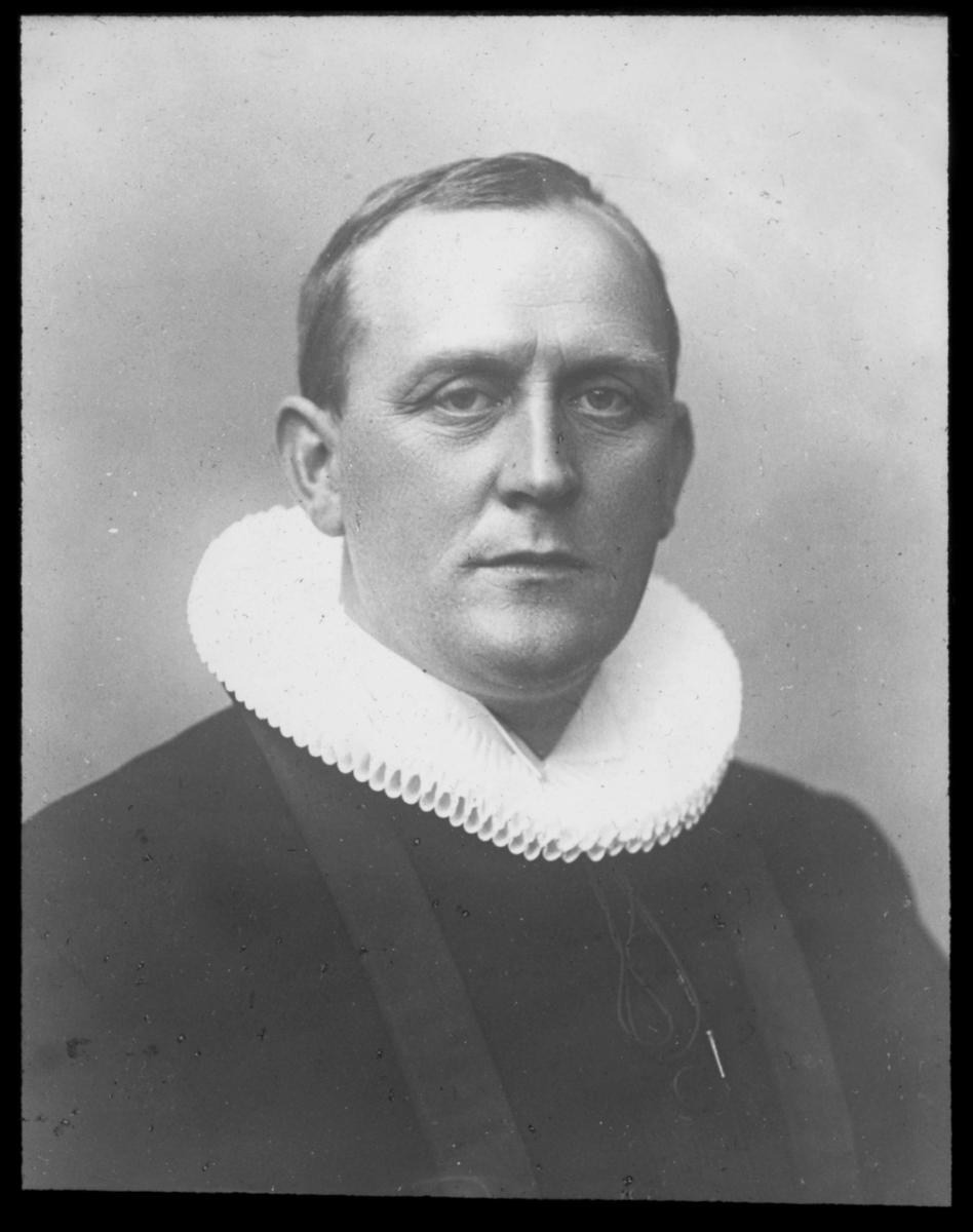 """""""S. sekretær sognep. S. Berg. G1"""" står det på glassplaten Portrett av sogneprest Sigurd Berg. Sigurd Berg ble i 1924 tilsatt som gen.sekr. i Finnemisjonsforbundet, med hovedkontor i Trondheim. Sognepresten bærer presteddrakt med hvit pipekrage og prestekjole."""
