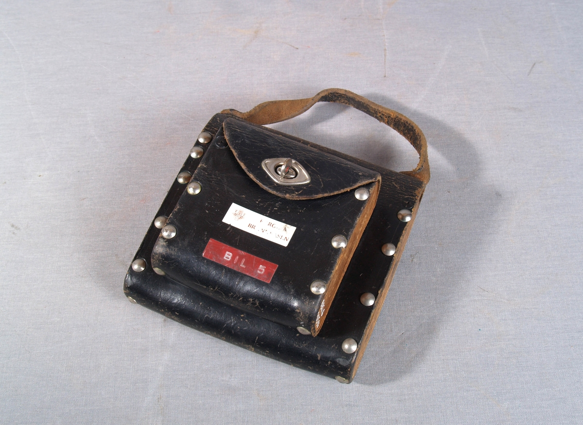 """Veske til oppbevaring av glassplater til brannmeldere. Vesken består av to rom montert sammen. Hvert rom har sidestykker i tre med lær spent rundt og festet med nagler. Lukkeklaff på fremsiden. Lærreim på toppen av det største rommet. Det største rommet inneholder 7 glassplater, det minste 2 glassplater og 7 merkelapper påtrykt """"Apparatet er ute av funksjon. Bruk telefon 001 Bergen Brannvesen."""