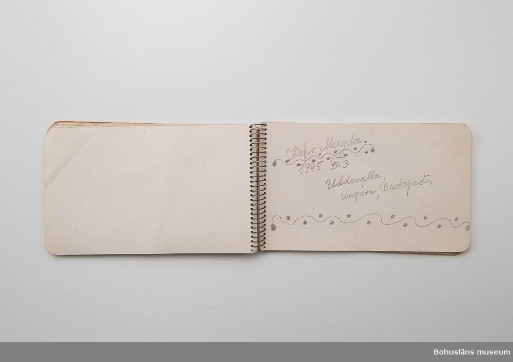 """Litet anteckningsblock, på omslaget med tryckt text: """"Autografer."""" På första sidan skrivet med blyerts:  """"Till minne från beredskapssjukhuset Juli – Augusti 1945"""". Skrivblocket innehåller uppslag med namn, teckningar och tillgivna poesiverser från patienterna. Varje person har ett eget uppslag. På sidan står namn och datum, i många fall hemort, teckningar, dekorationer, pressade växter. Vissa hörnflikar är nervikta, en har en gömd hälsning bakom; """"Jag älskar dig"""". Patienterna kommer huvudsakligen från Tjeckoslovakien, Polen och Ungern och är både kvinnor och män. Några av dikterna är av den polske poeten och nationalskalden Adam Mickiewicz. Anteckningsblockets samtliga sidor är fotograferade."""