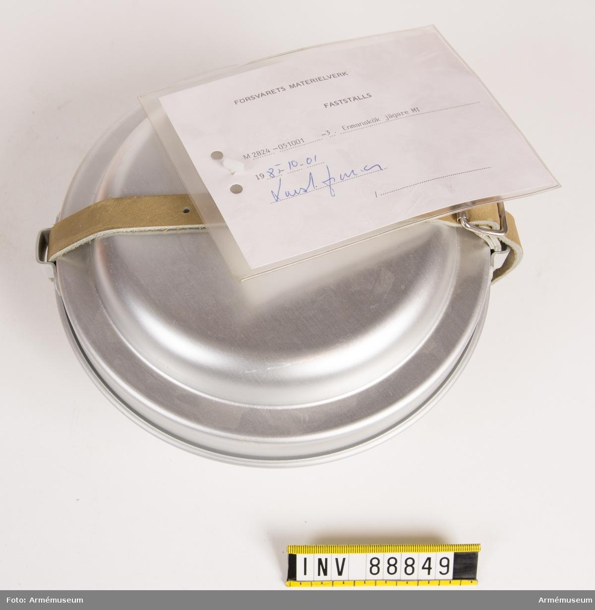 """Enmanskök bestående av en brännare, ett undre och ett övre vindskydd, två kokkärl; ett lock (stekpanna), lockhandtag, samt en omslagsrem av läder. På lockets ovansida märkt med tre kronor och NC 66 Svea. Vidhängande modellapp med text: """"Försvarets materielverk. Fastställs. M 2824-051001-3 Enmanskök jägare MT. 1985-10-01. (oläslig underskrift)."""""""