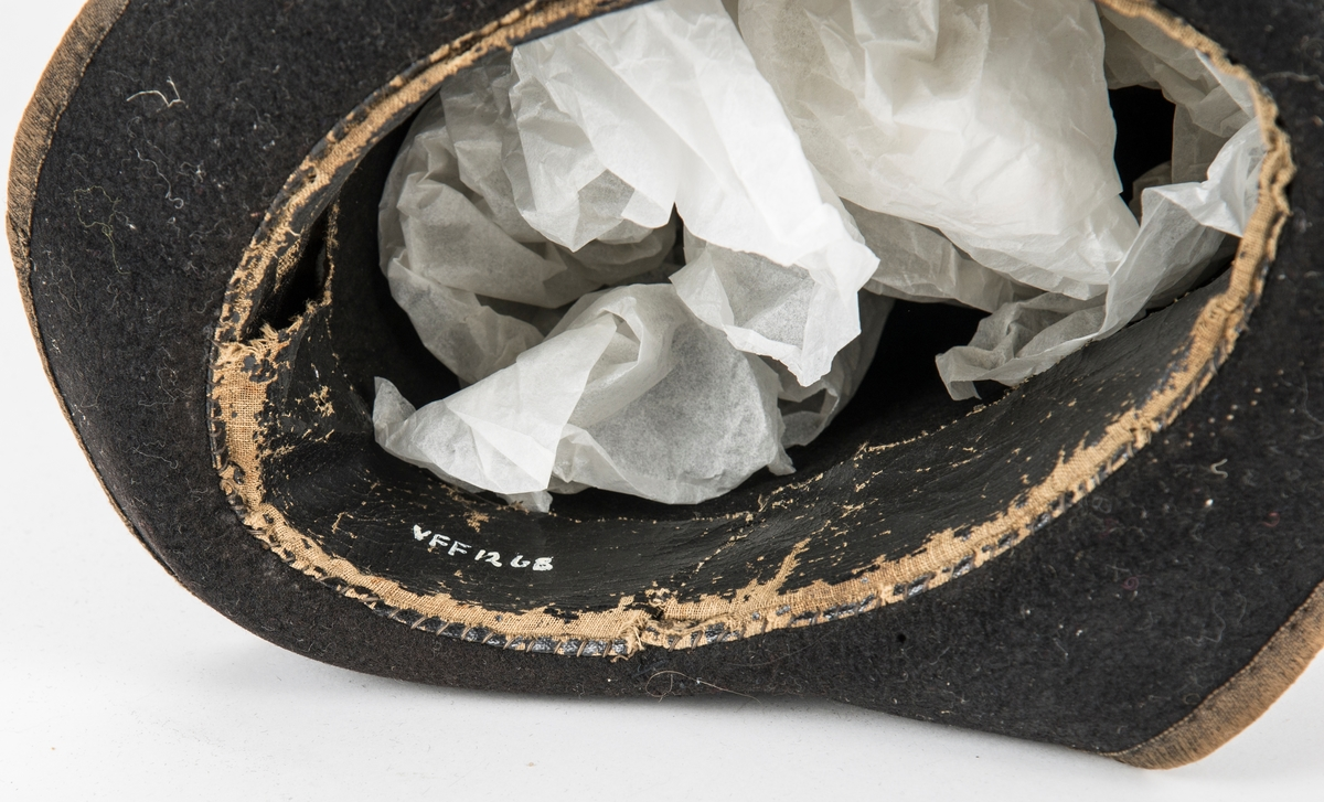 Hatt, høg svart flosshatt i silkefloss. Ripsband med ei spenne rundt pullen, kanta med ripsband rundt. Fóra inni med lerret. Saumen i pullen har gått opp, Mangar band på innsida av bremen. Stiva opp med papp.