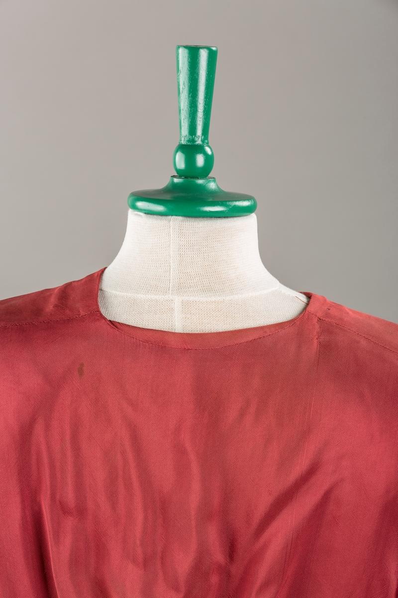 Form: Glatt, klokkeformet skjørt. Forstykkene rynket til buede bærestykker foran. Overdel rynket til skjørt. Korte ermer. Lukket med trykknapper. Belte fastsydd.