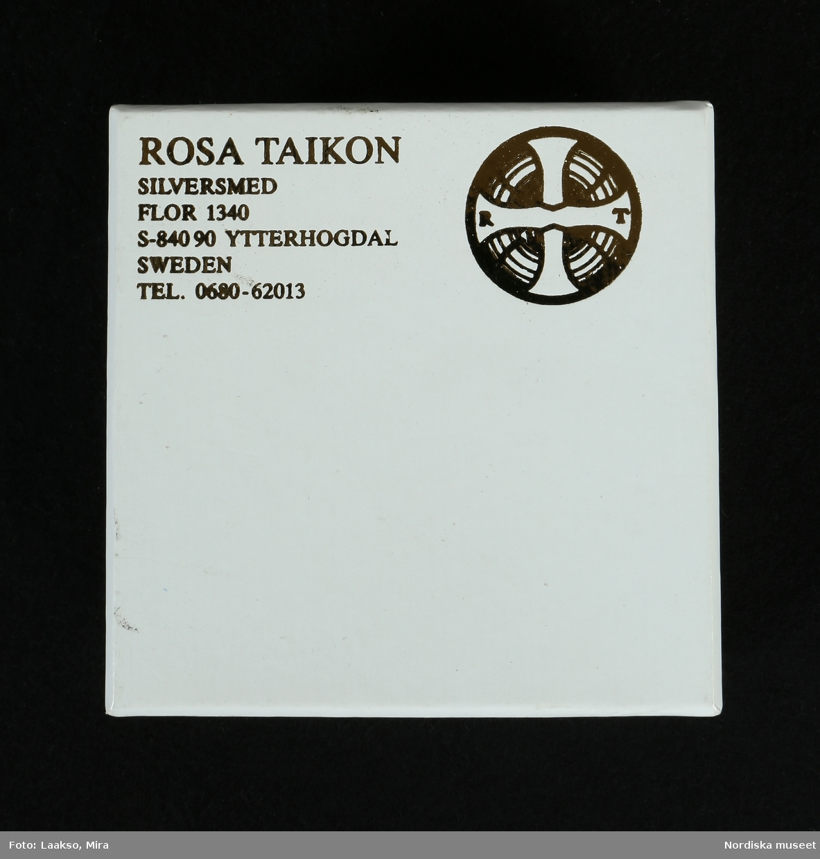 """Hängsmycke av silver, """"Moder jord"""" 925/2000, på dubbel silverkedja av platta länkar, spiralformad. Hängsmycket bestående av ett större och ett mindre klot, sammansatta med öglor av tvinnad silvertråd, det större klotet överst. Det mindre klotet avslutas nedåt med sex löst hängande kedjor av olika längd, spiralformade av samma slag som halskedjan.  Graverad på den större silverkulans nedre halva är Rosa Taikons signatur, samt silverstämplar. /Helena Lindroth & Petrine Knight, 2014-02-18"""