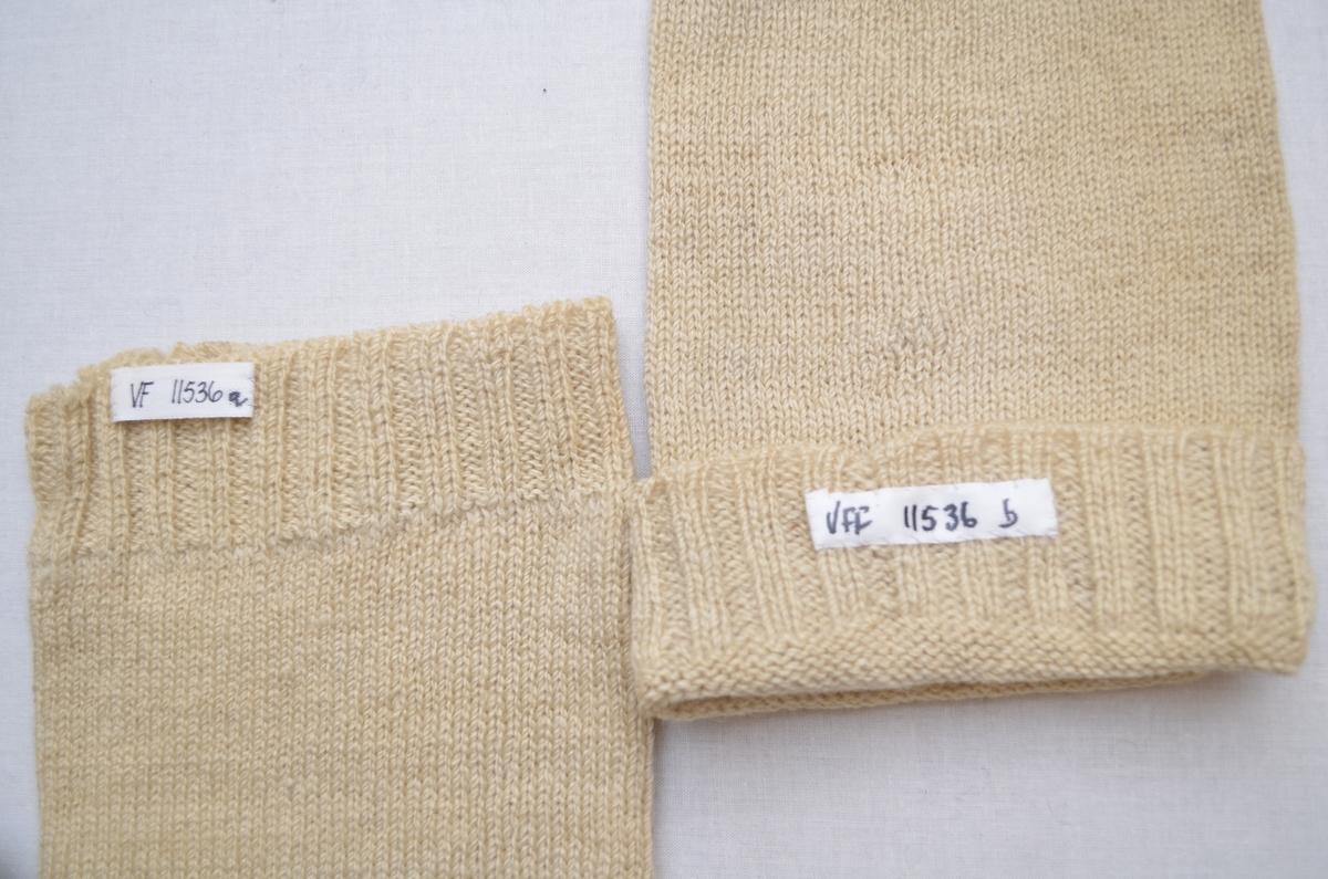 Lange strømper (a+b), hjemmestrikka i grått og ubleika hvitt hjemmespunnet ullgarn. Grå sokk, hvit legg. Vrangbord 2 rette og 2 vrange.