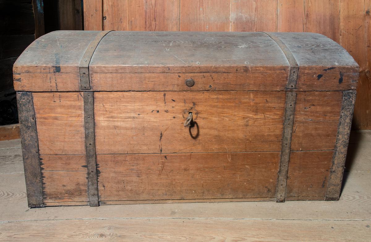 Kista av trä, rektangulär med välvt lock. Enkla beslag, gångjärn, handtag och nyckel av järn. Ingen inredning. Locket målat mörkt brunaktigt.