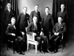 Grupporträtt på män i kostym och slips varav en person har f