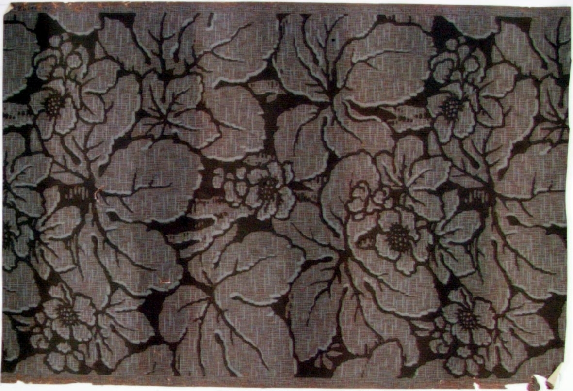 Stort sgrafferat blom-/bladmönster i grått och rosa på en brunbeige bakgrund.