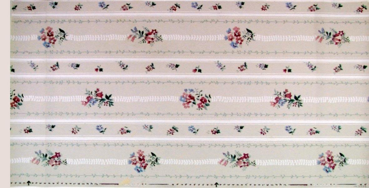 Randmönster dekorerat med naturalistiska blommor. Tryck i vitt, rött och grönt samt i flera pastellfärger på en ljusgrå bakgrund.