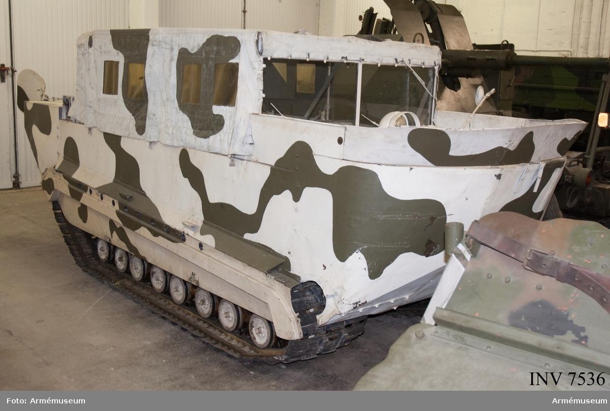 """Med flyttankar. Amerikansk beteckning M-29 C. Bandvagnen har tillhört Distrikstkommando Tröndelag Norge (se instruktionsbok för WEASEL (Snböbeltevogn M-29 og M-29 C) 1950 (A 110) och Bandvagn m/48).  I vänster fack i fören finns följande tillbehör:  - låda för kulspruteband, grönmålad av aluminiumplåt för tysk kulspruta MG 34 (jmf AM.004701), men här använd som tillbehörslåda med följande innehåll:  - generatorrem Optimat 17 made in Germany;  - fläktrem 3030-517-1134 Belt BA RD-A 860;  - 2 st tändstift """"Blue Crown Husky M-7""""; - plåtlåda med skumgummiinredning med 3 st lampor och 2 st säkringar;  - järntråd; - 5 st plugg för skrov 3/4"""" av järn, märkta: fyrkant, S,T,G ring m prick i; - plugg av mässing; - 12 st saxsprintar i brunt kuvert märkt: 42-P-5347 Splinter ass; - 4 st träkilar med kedja emellan 2 och de andra två löpande lösa på kedjan;  - 2 st kedjor med vardera fyra lösa ändar med vinkelhöjda (90 grader) krokar okänd användning,  - hänglås utan nycklar.  Lösa tillbehör i facket:  - länspump med slang;  - domkraft märkt: Drednaut 961 made in USA, med vev;  - domkraftsfäste för bandspänning (nya typen); - domkraftsfäste för boggi märkt 41-L-1392; - domkraftsfäste för boggi märkt 41-L-392 (vinklat järn).  I passagerarutrymmet: Bakom vänstra stolen på sidan en strålkastare (kan fästas på vagnens utsida) märkt: stort C med litet c i, 107406G, på underkant av glaset står BW i mitten av glaset GE (troligen General Electric);  - 2 st vinkeljärn som passar i hålen på passagerarutrymmets främre vägg, troligen radioanläggning.   En vit båtshake hänger på vänstra utsidan av vagnen."""