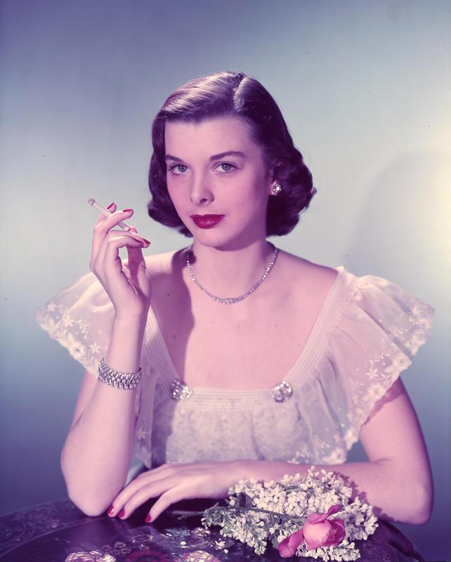 Reklamefoto. Kvinnelig modell i selskapsantrekk røyker en sigarett.