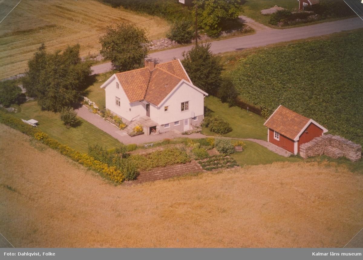 Bostadshus och sidobyggnad vid åkermarker i Arby socken.