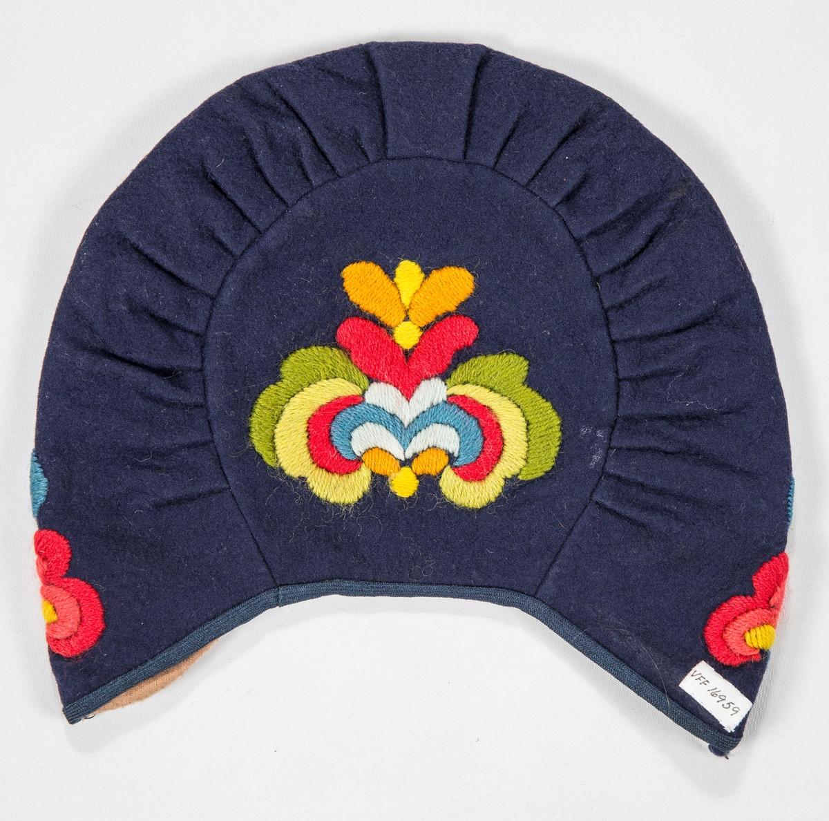 Bunadlue til hallingbunad (Huldra Garberg inspirert?) i blå ullfilt.  Brodert med ullgarn i blått, lyseblått, raudt, grønt, gult. Rund pull bak med eit foldelagt rett stykke rundt. Kanta med skråband. Fóra med rosa flanellstøy.