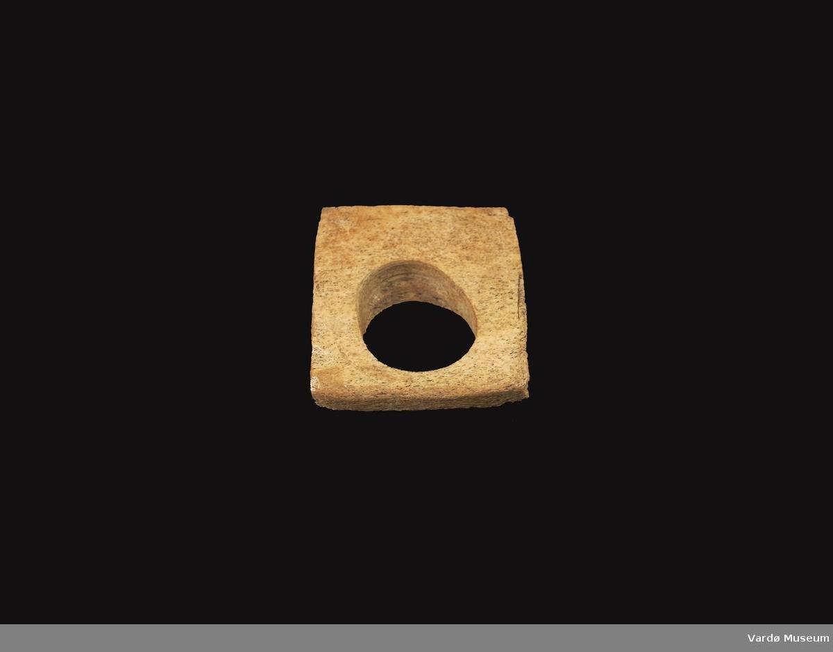 Firkantet og porøs, hull i midten på ca. 3,6 i diameter.