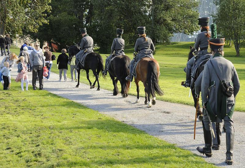 Fire ryttere i uniform som rir bortover en smal veg. Sett bakfra.