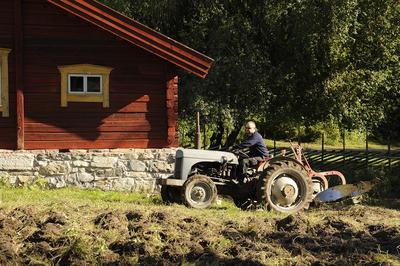 Mann på gråtasstraktor som trekker en plog, i bakgrunnen et rødt tømmerhus.