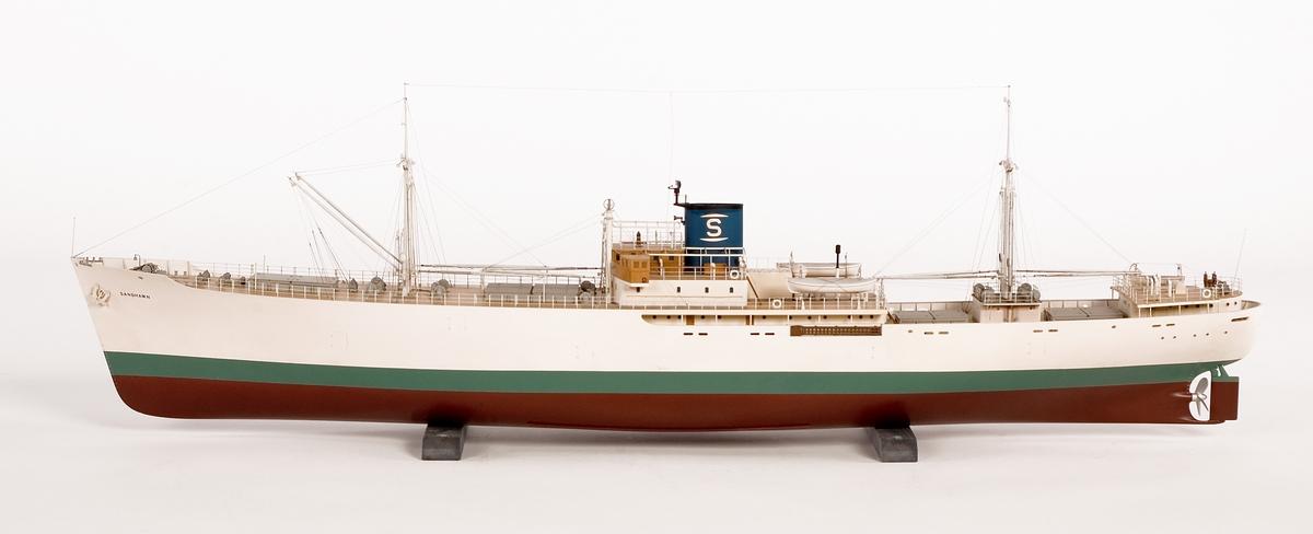 Helmodell av kyllastmotorfartyget SANDHAMN. Styrbords sida på modellen är öppen och visar lastrum och maskiner. Ettans lucka är tom för att interiören skall synas. I övriga lastrum finns stuvad bananlast. Blå skorsten med vit topp.