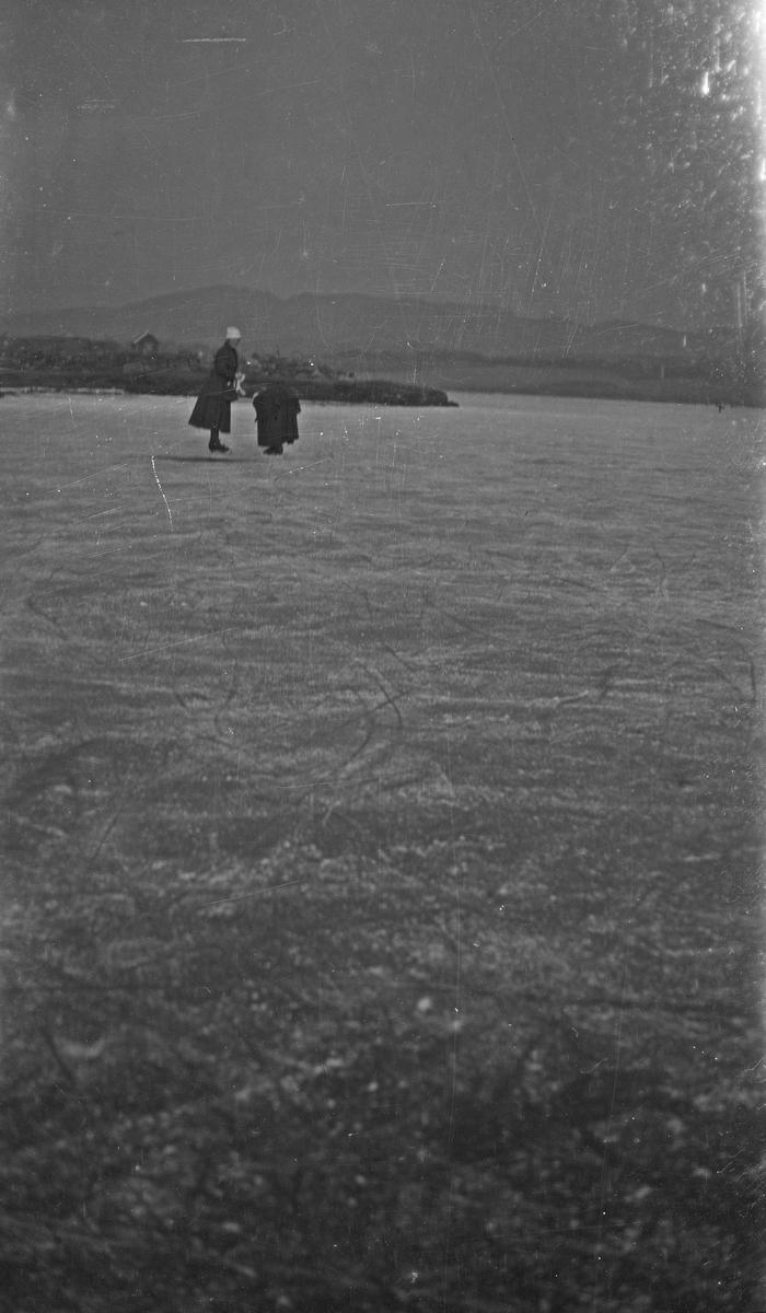 To kvinner på isen. Den ene kvinnen justerer skøyene sine. Hverdagsfoto.