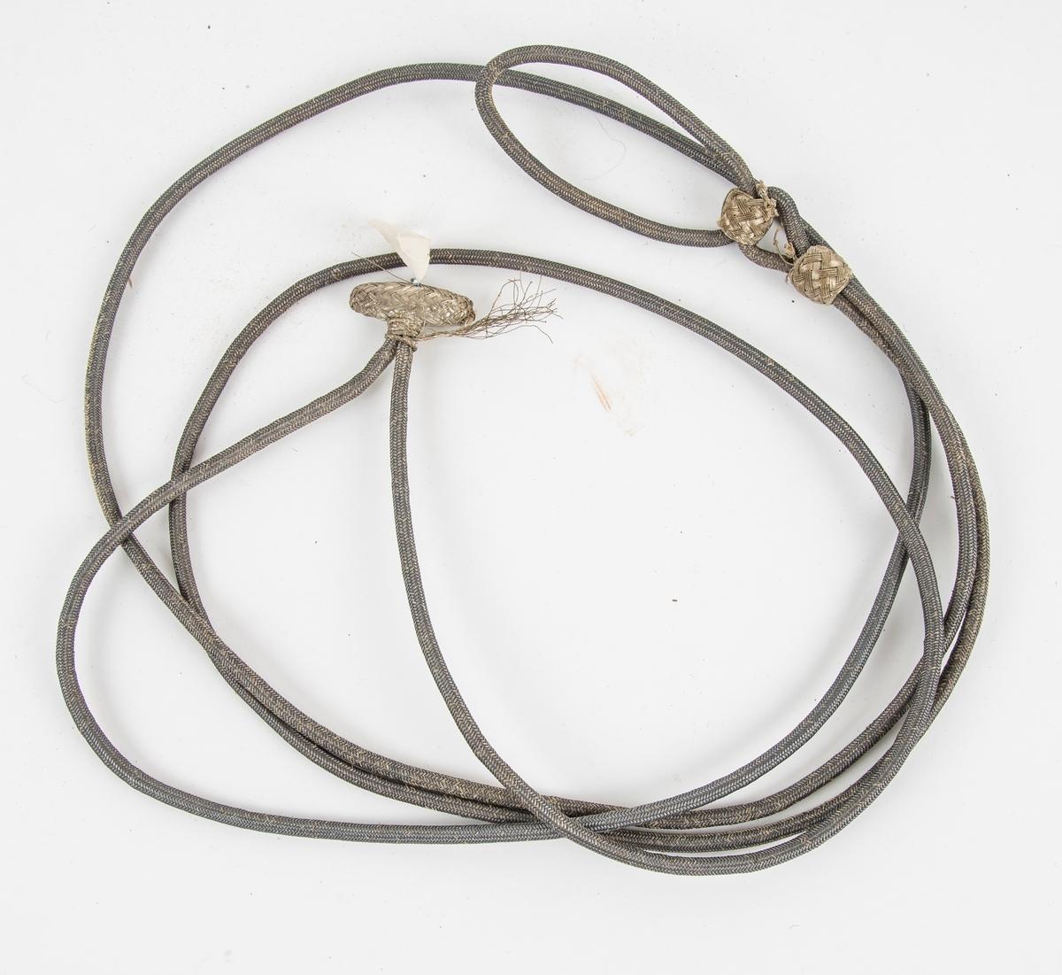 Snor i flette nysølv rundt eit bøyeleg materialer. I eine enden avlang knapp, også fletta. Lagt dobbel, den eine enden lengre enn den andre.