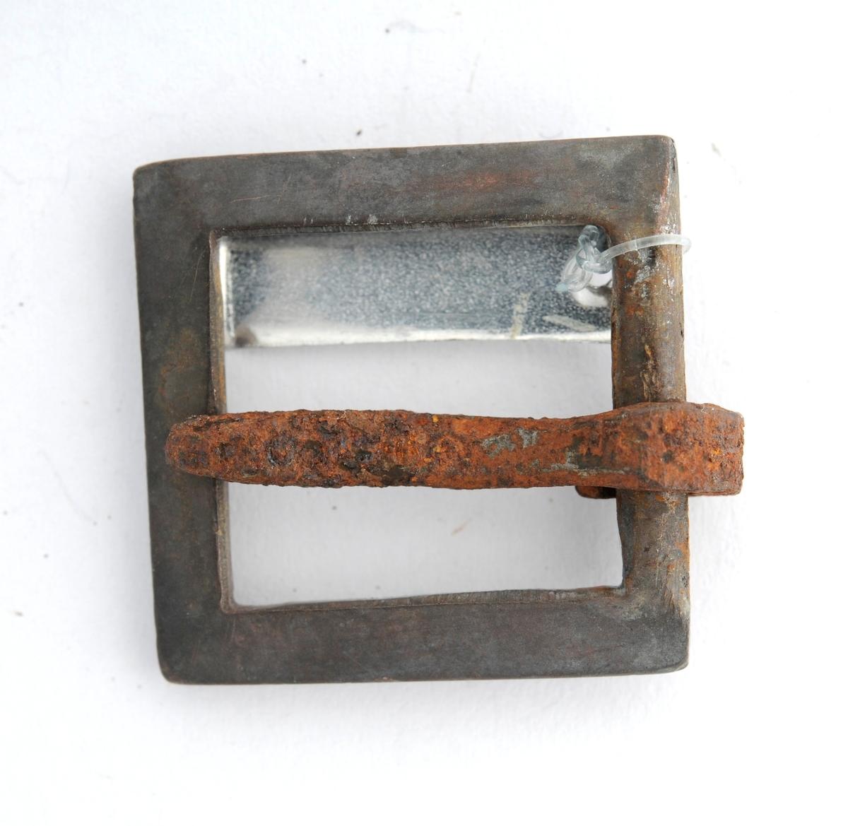 Spenne støypt i jern. Rektangulær form. Tann er smidd rundt stolpen på eine sida.