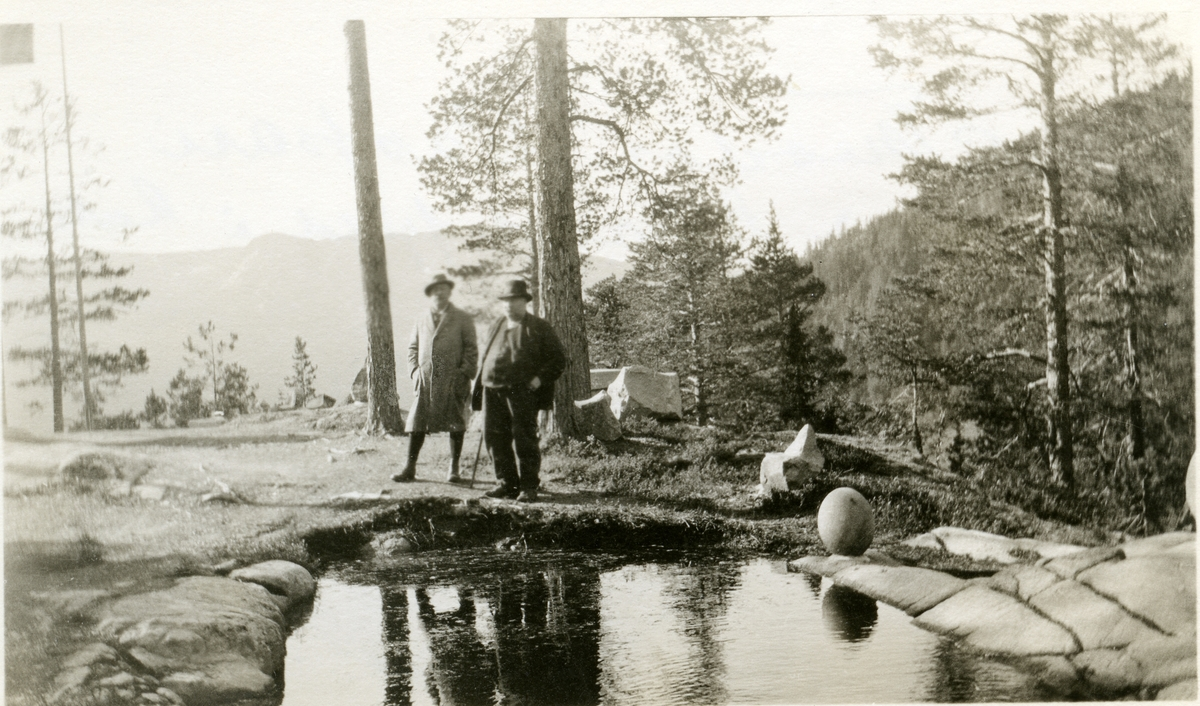 2 menn står ved en dam, med fjell og skog i bakgrunnen. Vatneberget. Den ene har stokk.