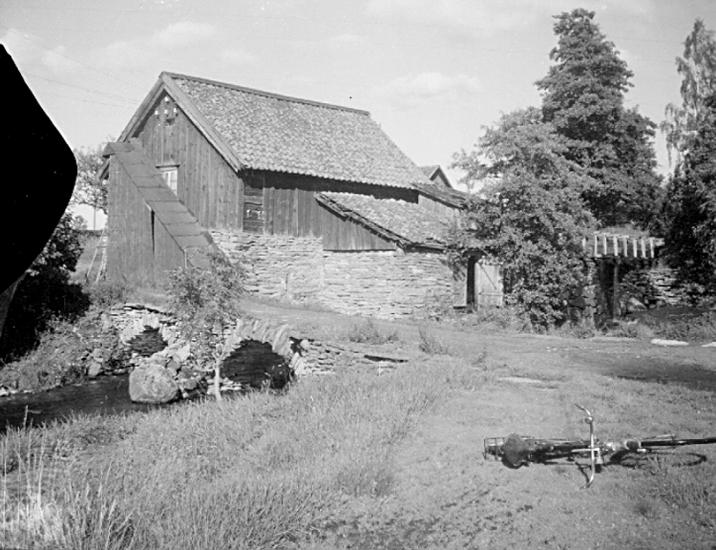 """Bildtext: Varnhems socken. Billekvarn på 1930-talet. I dagligt tal kallad """"Spetarskvarna"""", en dialektform av Hospitals kvarn. I 1699 års jordebok är antecknat: """"en kvarn vid klostret"""", som 1684 är taxerad och anslagen Skara hospital. I 1726 års jordebok redovisas även """"Billekvarn"""" anslagen Skara hospital"""". tydligen har här funnits två kvarnar, vilket även anges i kartbeskrivning 1864: """"Norra qvarn och södra qvarn"""". I 1825 års jordebok är antecknat att Häradshövding Jonas Lundin låtit uppbygga Billekvarn, som år 1724 blev Skara hospital anslagen, vidare att kvarnarna gå med ett par stenar vardera höst och vår samt att Klostrets kvarn och Bille kvarn sammanbyggts år 1823. Båda drevs som tullkvarnar. Sannolikt är kvarnhuset på bilden från 1823. 1 november 1942 skedde sista malningen av Otto Gustafsson. Kvarnen revs därefter."""