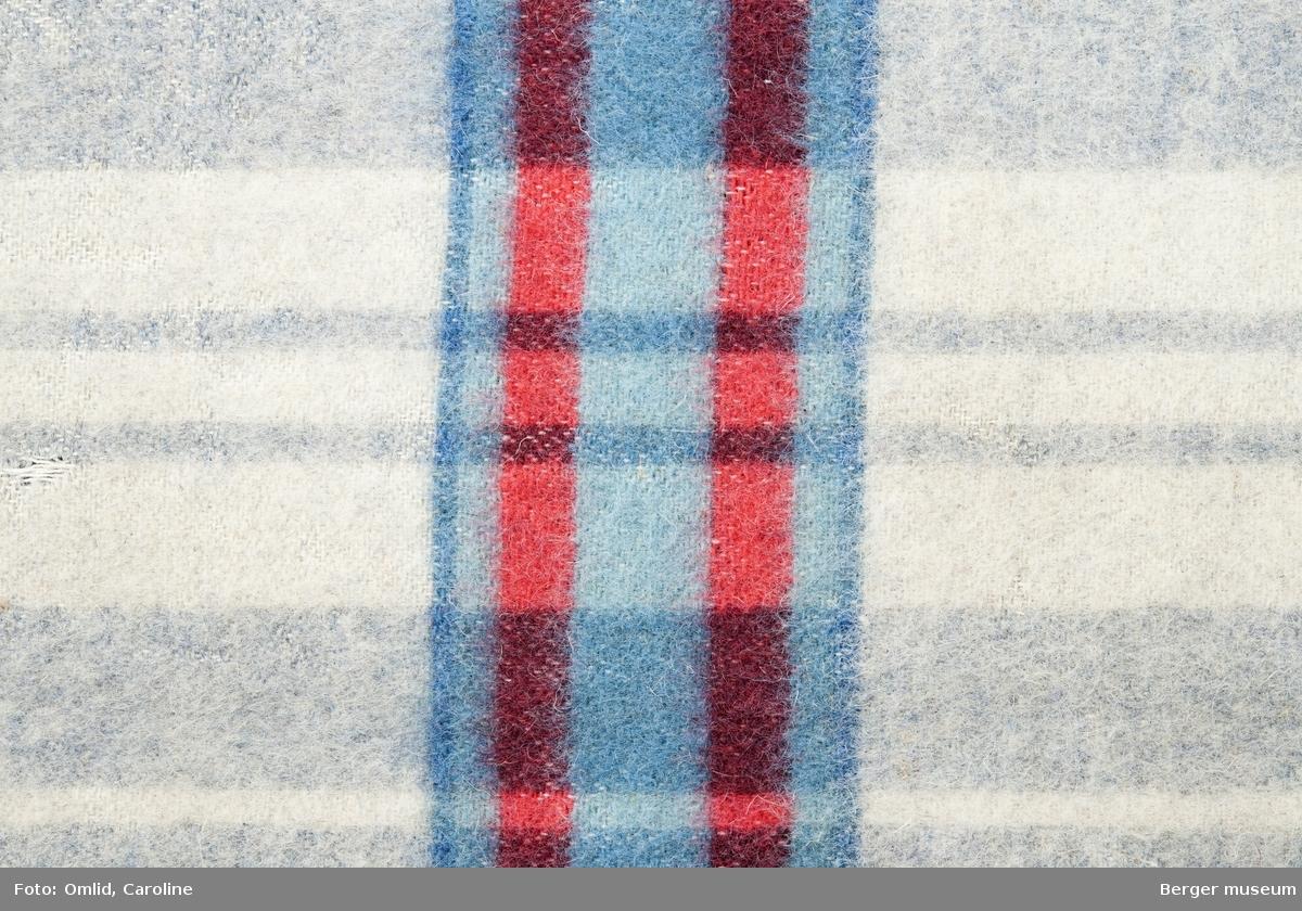 En prøve. Striper i grånyanser, med en tverrbord i rødt og blått.