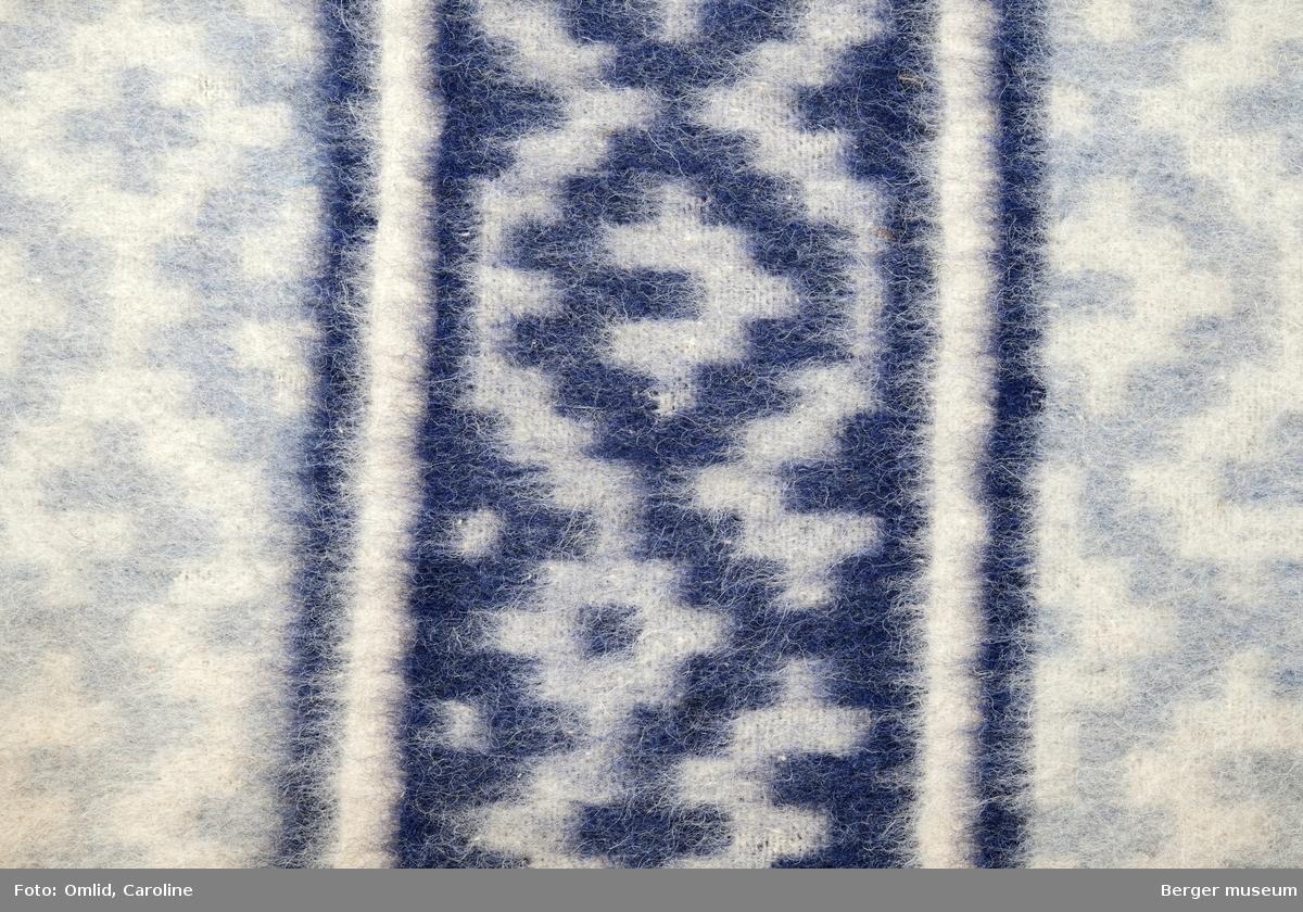 Teppeprøve med ruter utviklet fra korsmønster, med bord i liknende mønster innrammet av en stripe. Teppet i beige toner, borden i mørk burgunder.
