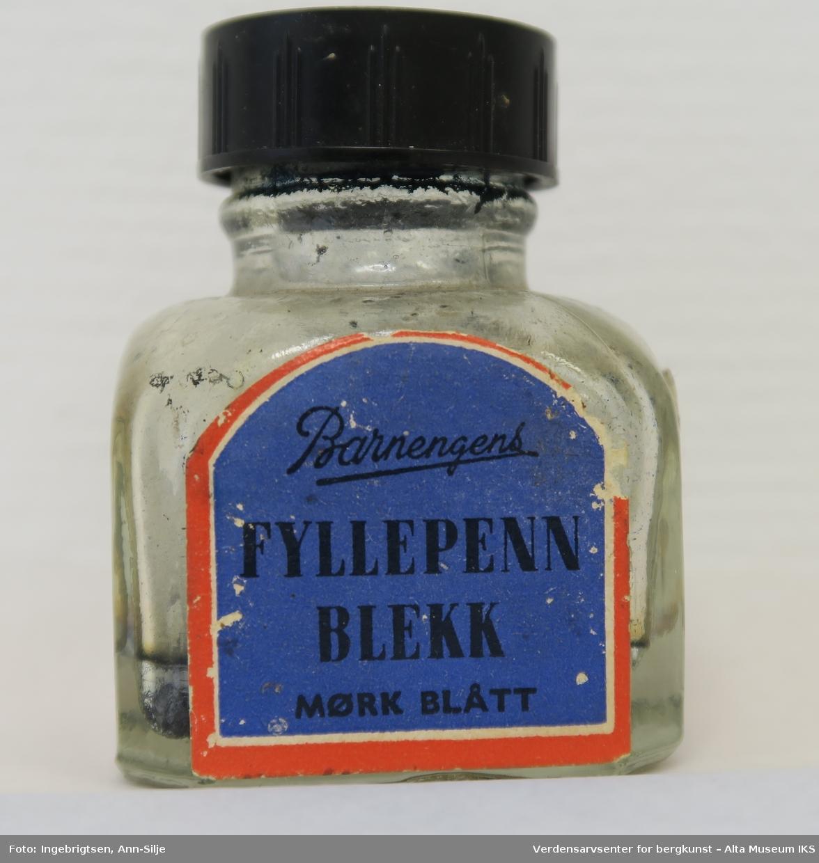 Liten flaske med kvadratisk grunnflate og rund tut. På den ene siden av flaska er det påklistret etikett.